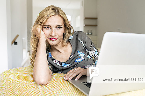 Portrait of a young woman with laptop on couch at home