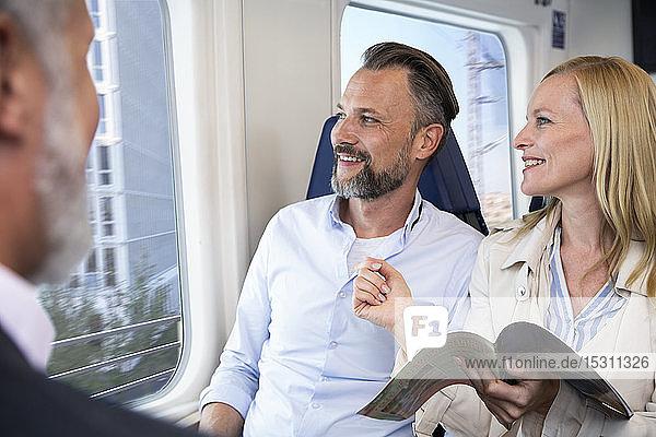 Ehepaar reist mit dem Zug  liest Zeitschrift