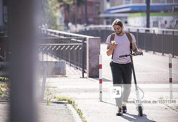 Junger Mann mit Elektroroller auf der Straße mit Handy