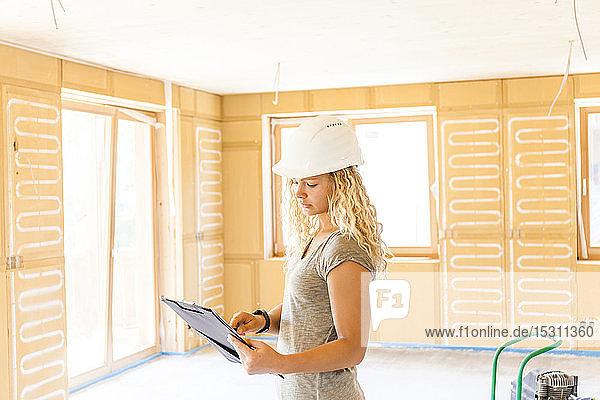Junge Frau prüft den Bau eines neuen Holzhauses