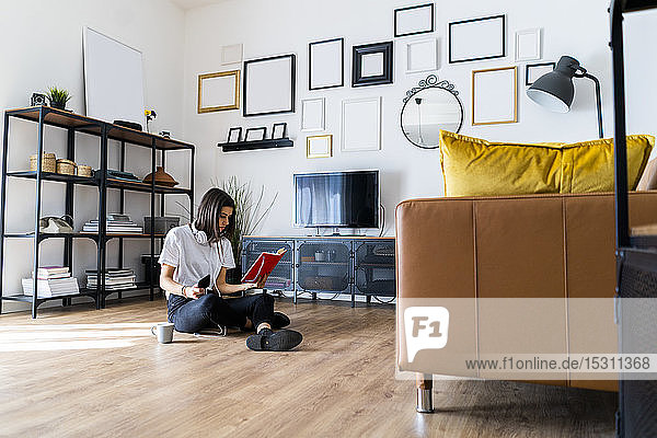 Young woman sitting on the floor at home reading a book