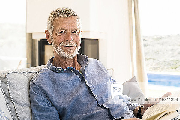 Portrait of smiling senior man reading a book at home