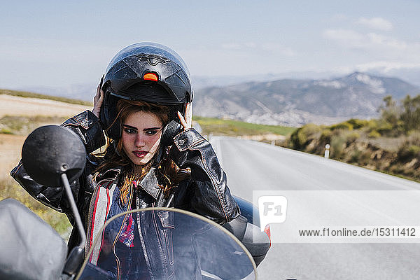 Portrait of motorcyclist putting helmet on  Andalusia  Spain