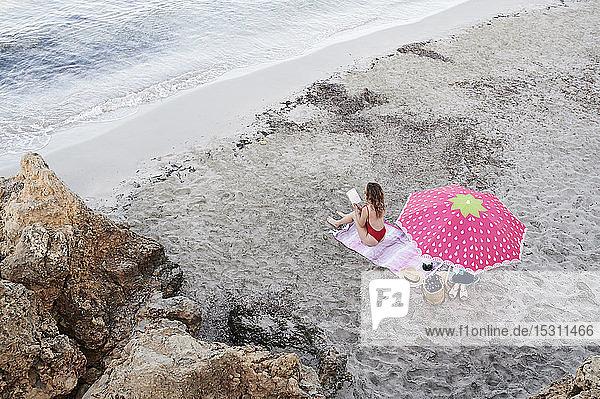 Junge Frau sitzt auf einem Handtuch am Strand und liest ein Buch