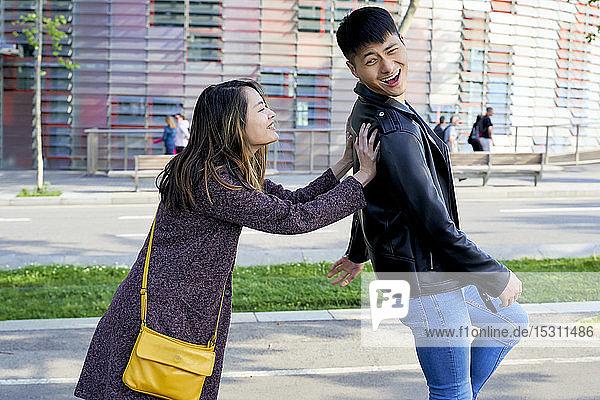 Happy woman pushing boyfriend down the street  Barcelona  Spain