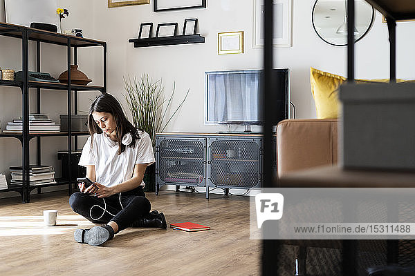 Young woman sitting on the floor at home using cell phone
