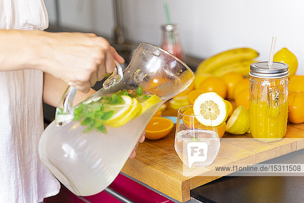 Nahaufnahme einer Frau  die zu Hause in der Küche Limonade in ein Glas gießt