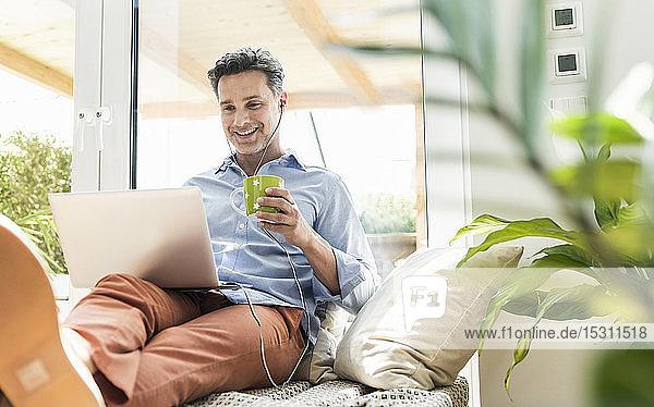 Reifer Mann sitzt auf der Couch  benutzt Laptop  trinkt Kaffee