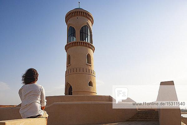 Rückansicht eines Mannes mit Blick auf den Sur-Leuchtturm  Oman