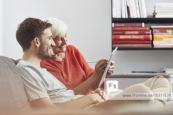 Grandson sitting on couch  using digital tablet with his grandmother