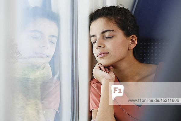 Teenagerin allein im Zug unterwegs  schlafend