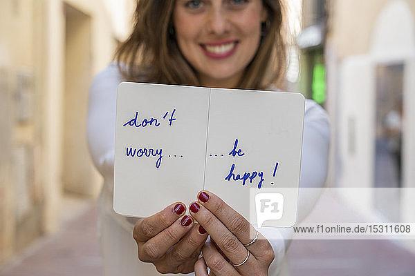 Porträt einer lächelnden Frau  die ein Notizbuch hält: Mach dir keine Sorgen  sei glücklich!