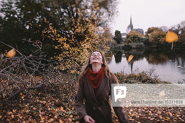 Happy woman playing with autum leaves