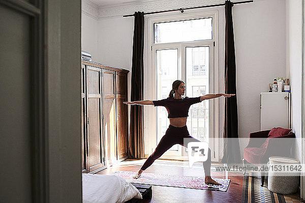 Junge brünette Frau praktiziert Yoga im Studentenwohnheim