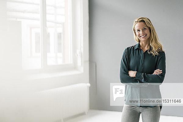 Erfolgreiche  blonde Geschäftsfrau steht in hellem Raum  die Arme verschränkt