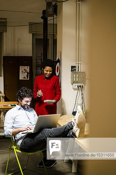 Businesswoman with businessman using laptop in office with feet on desk