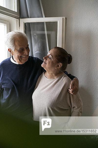 Glückliches älteres Ehepaar am Fenster zu Hause