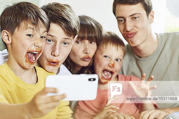 Mutter und ihre vier Söhne mit Smartphone-Selbstfahrern beim Mittagessen  mit Gesichtern voller Tomatensauce
