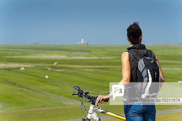 Deutschland  Schleswig-Holstein  Sankt Peter-Ording  Frau mit Fahrrad  die in die Ferne schaut