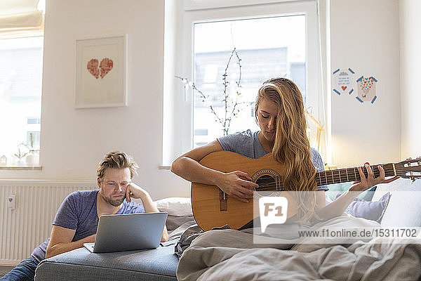 Young woman at home playing guitar with damaged string with partner using laptop
