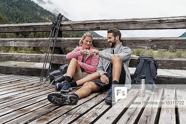 Young couple having a break on a wooden bridge during a hiking trip  Vorderriss  Bavaria  Germany