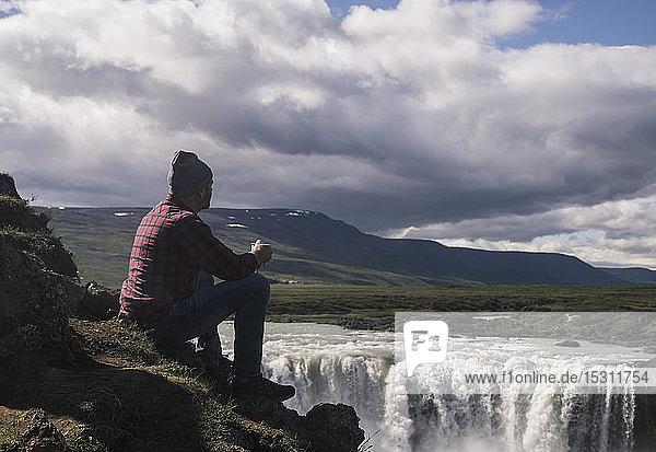 Mann sitzt mit einer Tasse Kaffee und schaut auf die Godafoss-Wasserfälle  Island