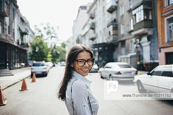 Porträt einer glücklichen jungen Geschäftsfrau auf der Straße