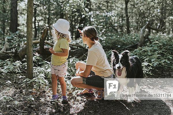 Mutter mit Tochter und Hund in einem Wald