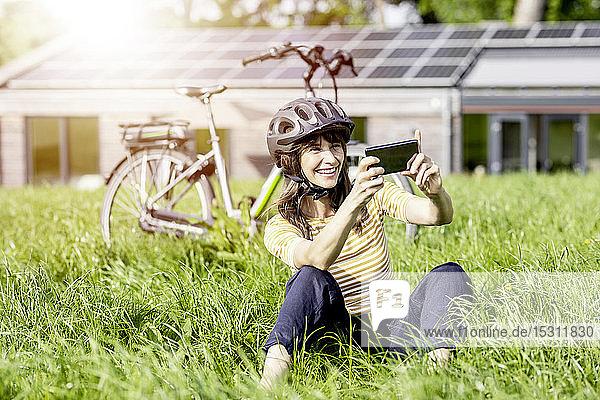 Glückliche Frau sitzt mit dem Fahrrad auf einer Wiese und macht einen Selfie