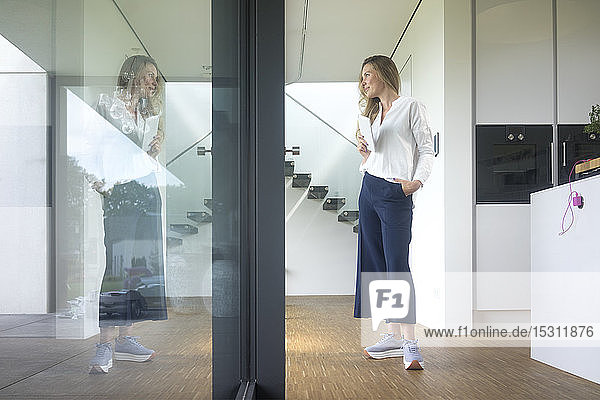 Businesswoman holding tablet in modern home looking out of window