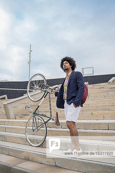 Stilvoller Mann mit Fahrrad auf der Treppe in der Stadt