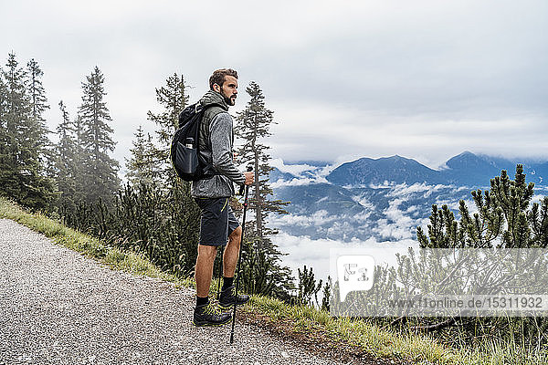 Young man on a hiking trip in the mountains looking at view  Herzogstand  Bavaria  Germany