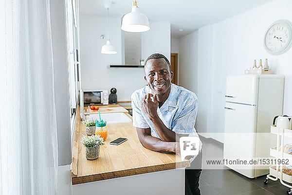 Porträt eines lächelnden jungen Mannes in der heimischen Küche