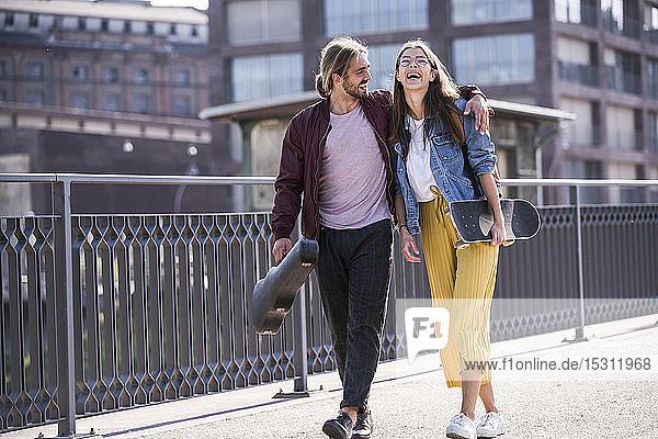 Glückliches junges Paar mit Skateboard auf einer Brücke