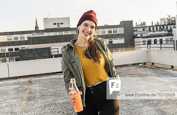 Porträt einer glücklichen jungen Frau mit Kopfhörern und Getränk auf dem Parkdeck