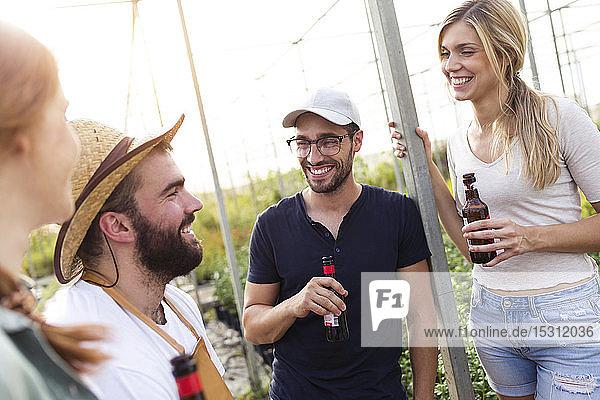 Eine Gruppe von Freunden trinkt Bier und genießt die Zeit im Gewächshaus