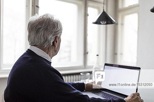 Älterer Mann benutzt Laptop zu Hause auf dem Tisch