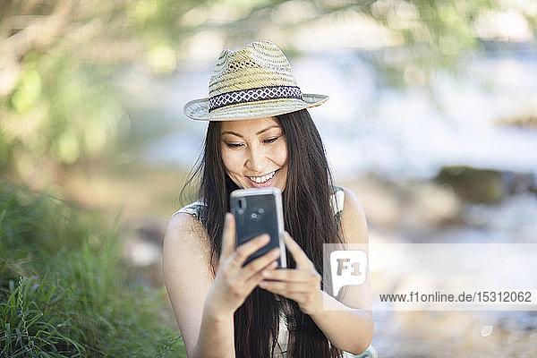 Lächelnde junge Frau  die einen Strohhut trägt und ihr Smartphone draußen benutzt