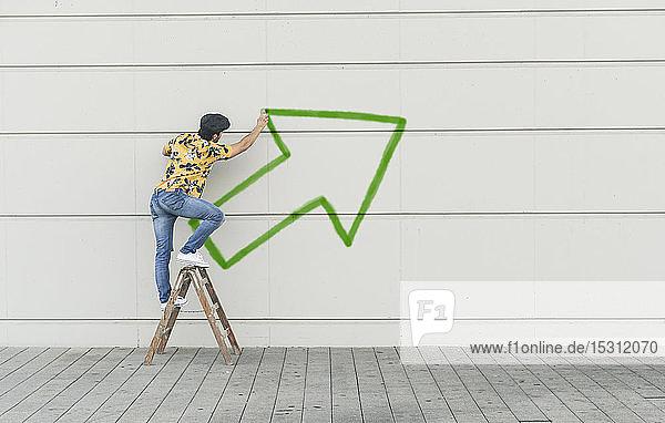 Digitale Komposition eines jungen Mannes  der einen Pfeil an eine Wand zeichnet