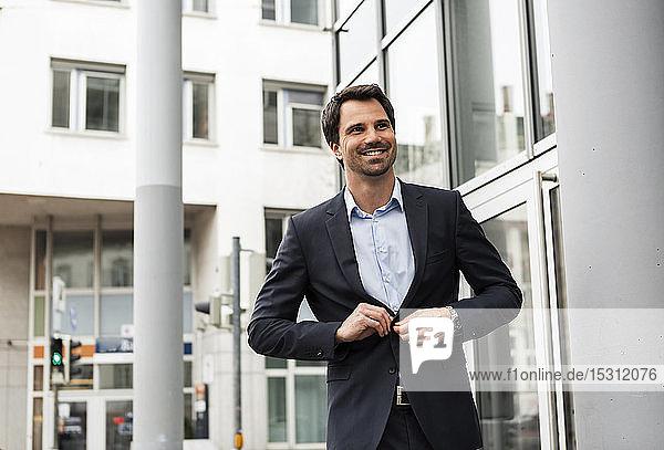 Porträt eines lächelnden Geschäftsmannes  der seinen Anzugsmantel zuknöpft