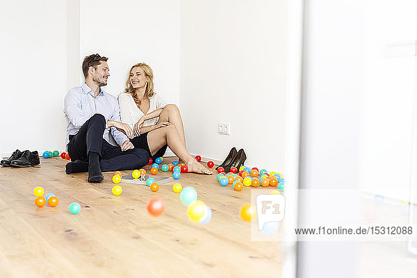Glückliches Paar in Businesskleidung sitzt auf dem Boden  umgeben von bunten Bällen