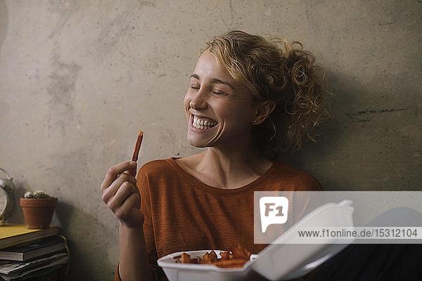 Porträt einer grinsenden jungen Frau  die zu Hause Pommes Frites isst