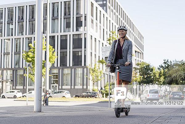Glückliche Geschäftsfrau fährt Elektroroller auf der Straße