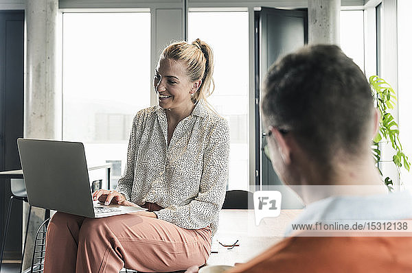 Smiling businesswoman sitting on table in office using laptop with businessman in foreground