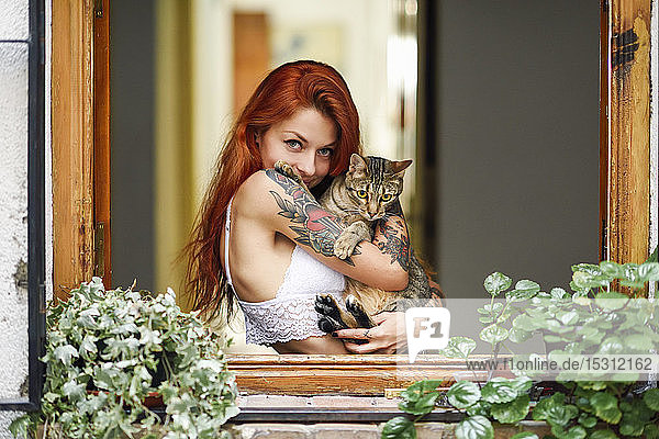 Porträt einer rothaarigen tätowierten Frau mit ihrer Katze am Fenster