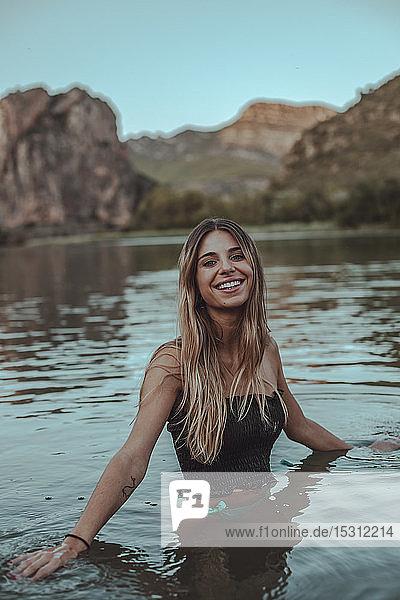 Junge blonde Frau  die im Sommer abends in einem See badet
