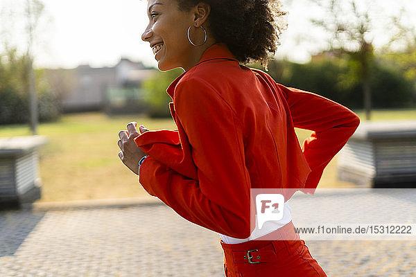 Laufende junge Frau im modischen roten Hosenanzug