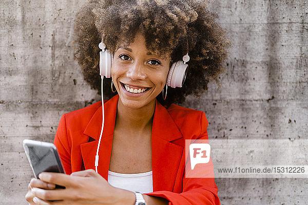 Porträt einer lächelnden jungen Frau mit Smartphone und Kopfhörer