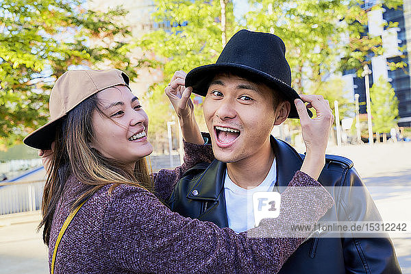 Portrait of playful couple wearing hat and cap