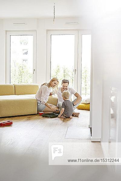 Glückliche Familie mit einem Sohn  der im Wohnzimmer ihres neuen Zuhauses spielt
